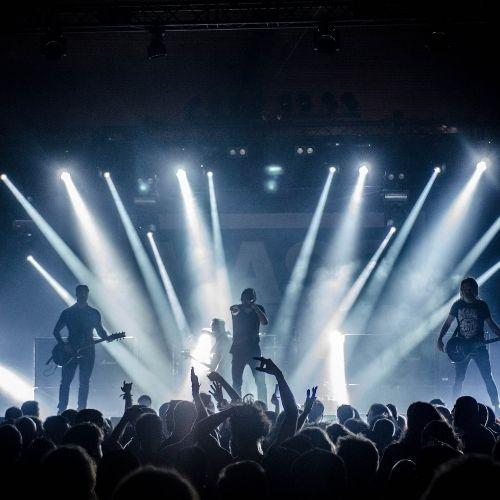 Een band speelt op een podium met een hele hoop mensen in de zaal