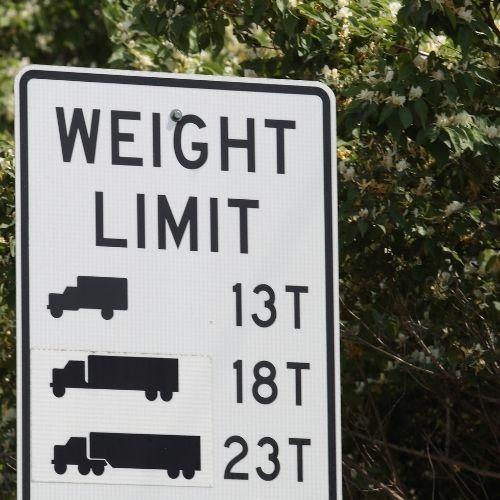 Verkeersbord met 'Weight limit' erop en drie afbeeldingen van vrachtwagens in verschillende groottes