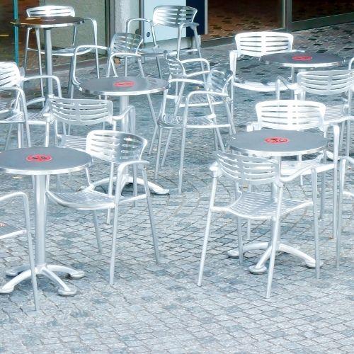 Een terras met metalen tafels en stoelen die een leuning hebben